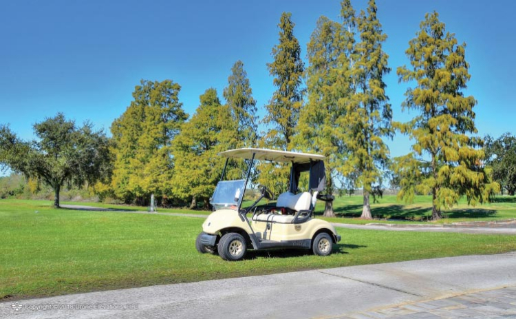 A golf cart sits just off the path at Cypresswood Golf & Country Club